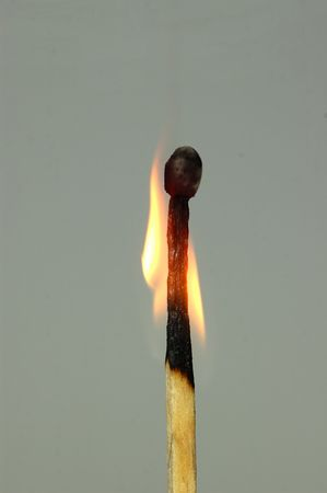 A burning matchstick isolated against a gray background