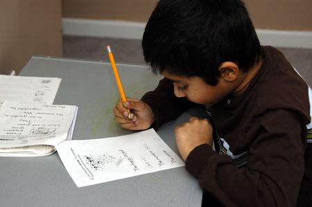 A Kid diligently doing his school homework Stock Photo