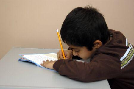 Un niño con diligencia haciendo su tarea escolar  Foto de archivo - 780901