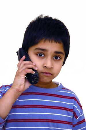 A kid speaking to some one over the phone photo