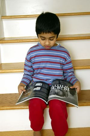 A handsome young kid reading a magazine Stock Photo - 780871