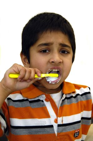 dentalcare: a kid diligently brushing his teeth