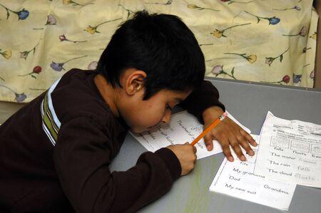 Un niño con diligencia haciendo su tarea escolar  Foto de archivo - 780876