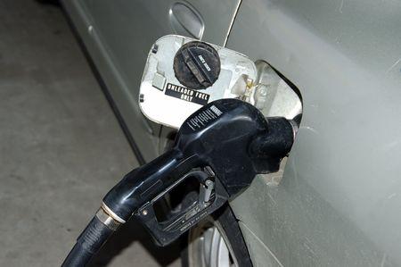 A gray automobile at a gas station pumping gas Reklamní fotografie