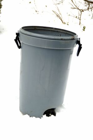 Trash can isolated on a snow back ground photo