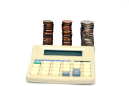 Piles of coins isolated on a white background with calculator intentionally blurred in the foreground Stock Photo - 789169