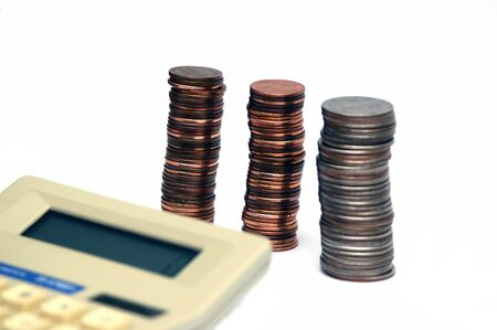 Piles of coins isolated on a white background with calculator intentionally blurred in the foreground Stock Photo - 789168