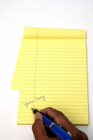 A yellow notepad and a pen isolated against a white background