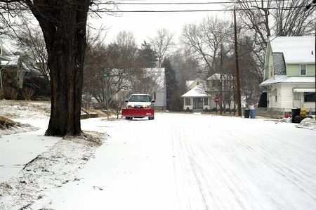 A small snow plow clearing a road photo