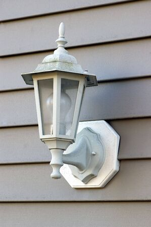 A porch light against a brown vinyl siding
