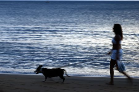 A young woman walking her dog on the beach blur depicting motion photo