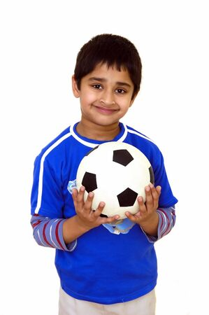A young handsome kid holding a soccer ball