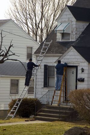 Two male workers fixing the roofing in a old house photo