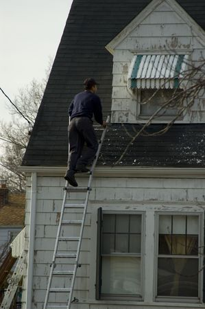 A male worker fixing the roofing in a old house photo