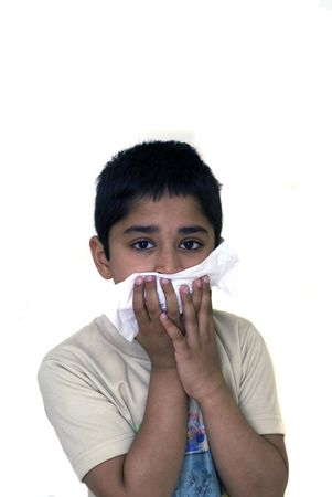 handsome boy: A young handsome boy with a tissue to his nose nurses a cold