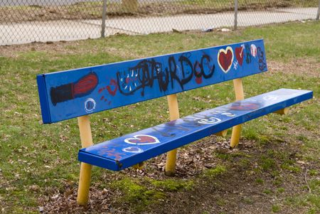 Grafitti on an old blue park bench