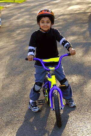 A young indian kid having fun riding a bike photo