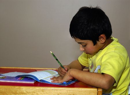 An handsome Indian kid diligently doing his homework photo