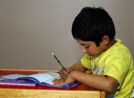 tarea escolar: Un chico guapo indio haciendo diligentemente su tarea