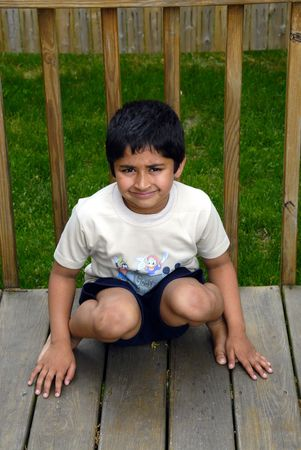 an unhappy indian kid sitting on a deck photo