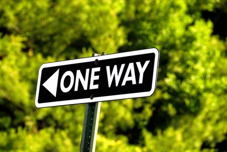 One way road sign againt a green back ground Stock Photo - 2006574