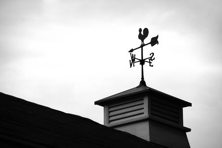 Siloutte of a wind direction at the top of a roof
