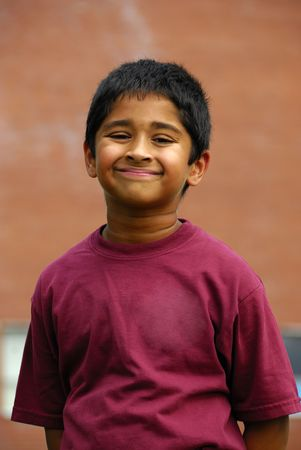 A happy Indian school kid smiling in front of the classroom photo