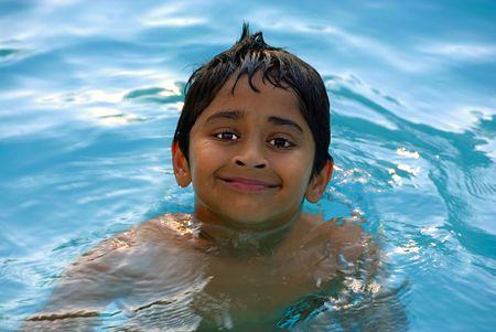 楽しんで若いインドの少年はプールで泳いでいます。