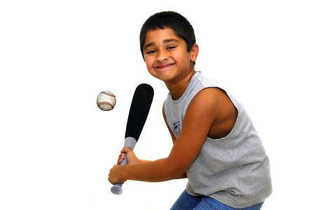 Young handsome indian kid having fun hitting ball Stock Photo