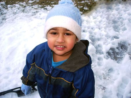 An Indian kid enjoying the snow after a blizzard