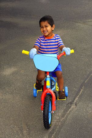 soft pedal: An handsome Indian kid enjoying his bike Stock Photo