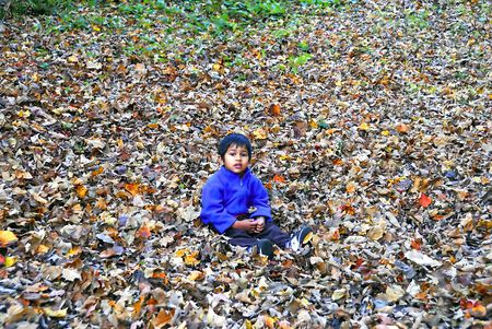 an handsome indian kid enjoying himself sitting on the fallen foliage photo