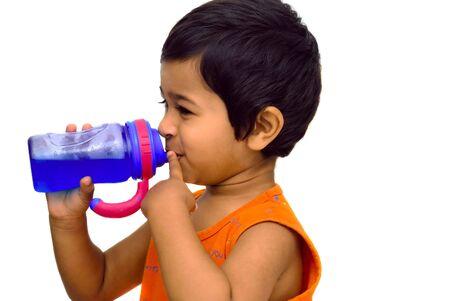 replenish: An handsome indian kid having fun drinking juice Stock Photo