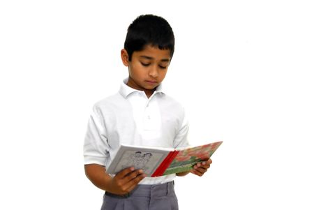 an handsome indian kid reading a book at school