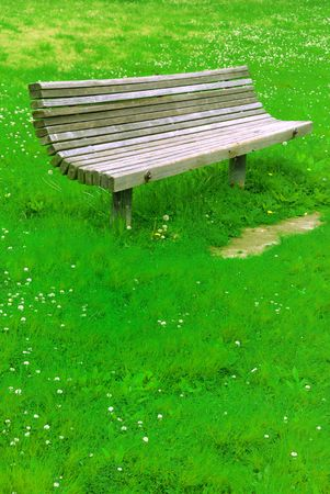 an old park bench isolated on grass back ground photo