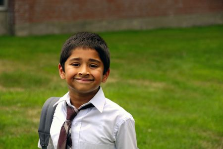 A happy Indian school kid smiling in front of the classroomr
