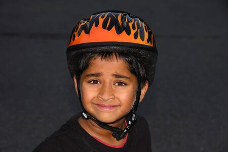 An handsome Indian kid wearing an helmet for safety photo