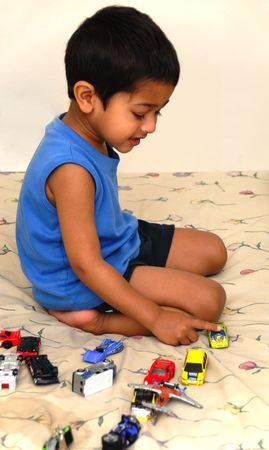 Handsome little boy playing with toy car in bed Banco de Imagens