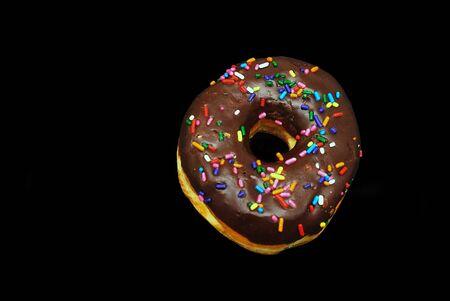 Tasty sprinkles chocolate dounut on a black background photo