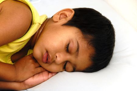 An young kid lying in bed feeling very sick Stock Photo