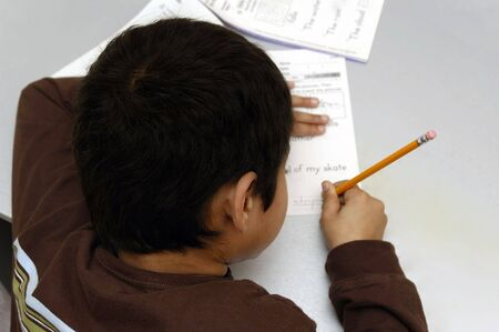 A handsome kid doing his homework diligently Stock Photo