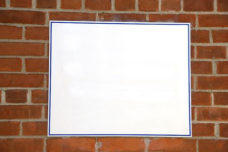 advertize: A blank white sign board against a brick wall ready for your text Stock Photo