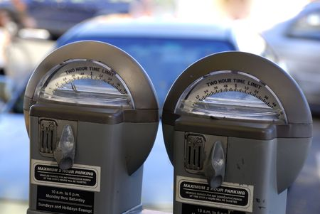 tardy: PArking meters againt a shallow depth of cars parked at the background