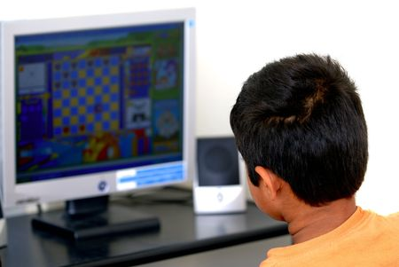 An young kid playing games at the internet photo