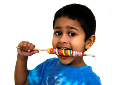 An handsome Indian kid savoring his colorful candy photo