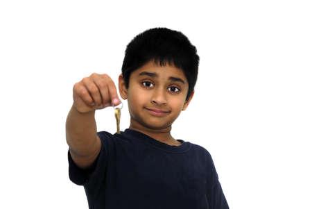 An handsome Indian kid handing over keys photo