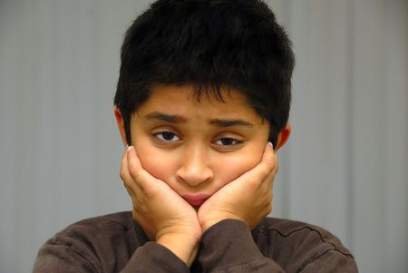 An handsome Indian Kid in a very sad mood Stock Photo