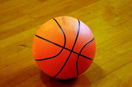 basketball in the spotlight resting on the hardwood floor photo