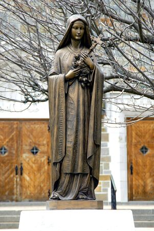 A metalic statue of Virgin mary in front of a catholic church photo