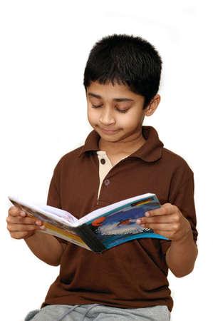 An adorable boy reading his school book photo